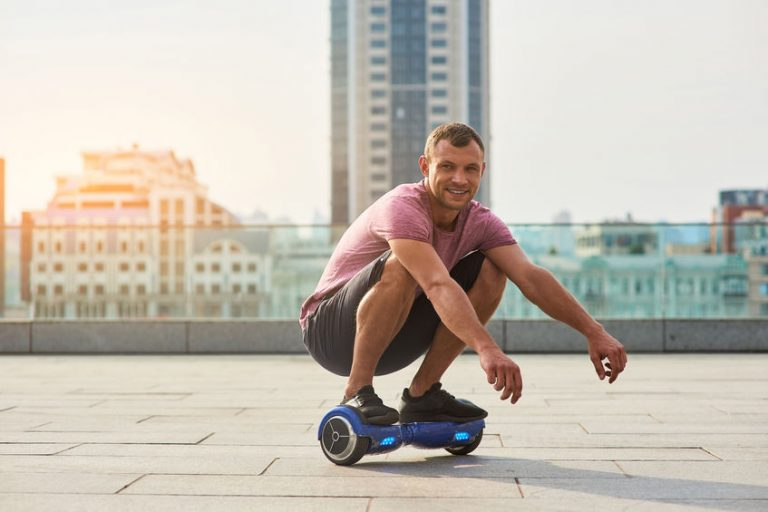 Smiling man on hoverboard.