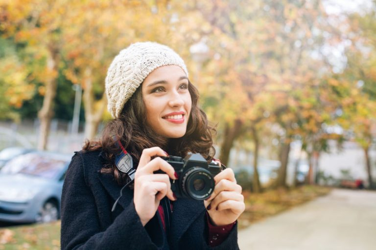 woman smiling with canon camera outdoors