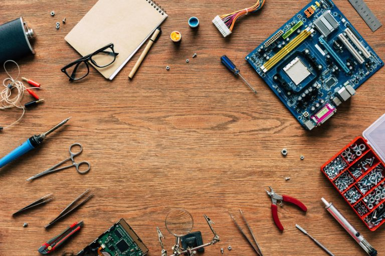 top view of repairing tools and microschemes on wooden table