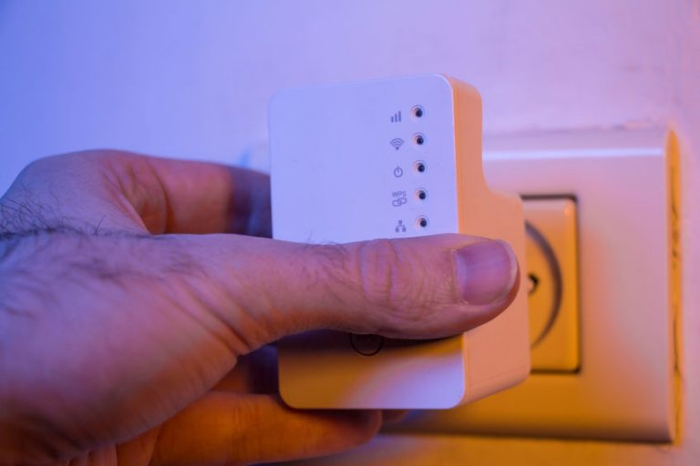 Man insert WiFi repeater into electrical socket on the wall