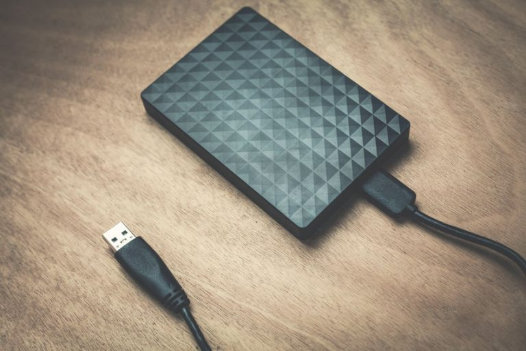 Black external hard drive on wooden surface